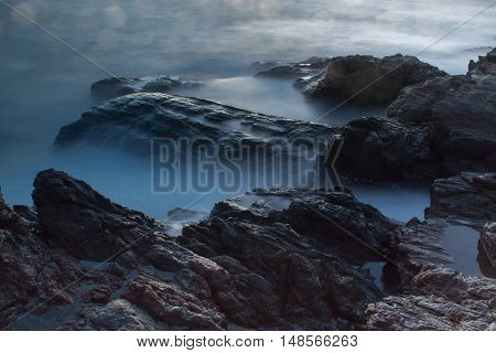 Ocean waves crashing onto the rocks in the sunset