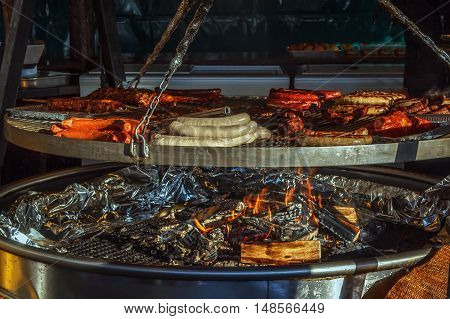 Grilled sausages of different kinds on big hanging grill at Christmas market in Frankfurt am Main Germany