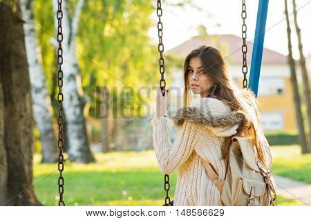 Female student in sweater on a swing in park with backpack. Beautiful young teenage girl in beige knitted sweater, outdoors on sunny fall day with backpack. Natural light, no retouch.