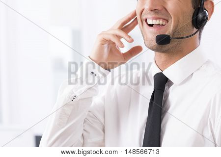 Shot of a young call center agent talking to his microphone
