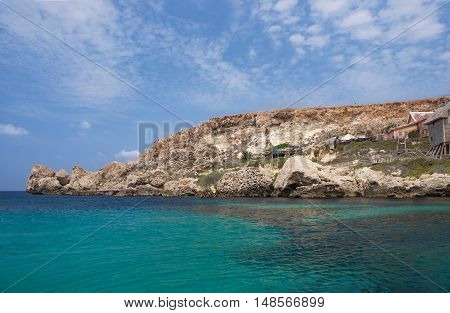Panoramic view of Popeye Village in Malta with nice blue sky and emerald sea background. Popular tourist destination in Malta - Popeye Village