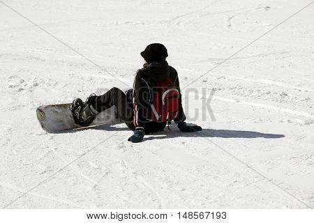 Girl snowboarder siting on fresh powder snow