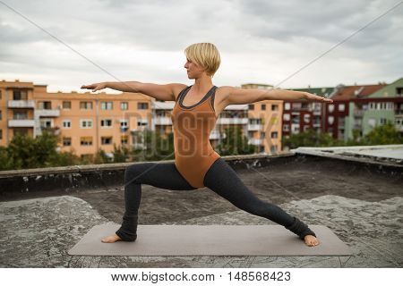 Beautiful woman practicing yoga on the roof,Virabhadrasana/Warrior pose