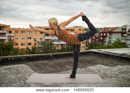 Beautiful woman practicing yoga on the roof,Natarajasana / Shiva posture