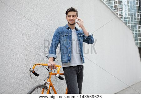 Smiling guy in denim jacket with beard and orange bicycle standing on the background of white wall. Student calling on the phone