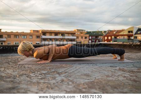 Woman practicing yoga on the roof,Chaturanga Dandasana/Four-Limbed Staff Pose