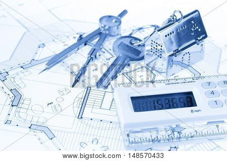 key with keychain in the form of a silver-colored house on a background of architectural drawing, electronic calculator &  compass