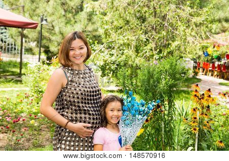 Happy pregnant asian mom and child girl hugging. The concept of childhood and family. Beautiful Mother and her baby outdoor