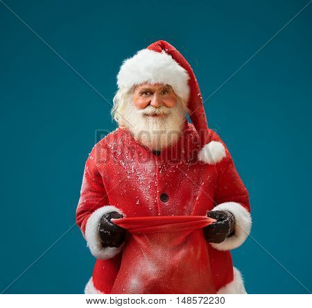 Smiling Santa Claus with christmas present and looking at camera. Merry Christmas & New Year's Eve concept. Closeup on blue background.
