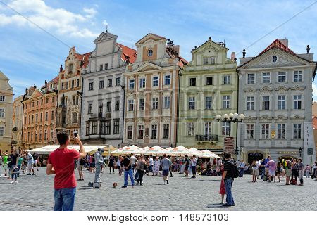 PRAGUE, CZECH REPUBLIC - JULY 3, 2014: Tourists enjoy the beauty of the old colorful houses in the Historic Old town square. Prague is Europe's 5th most visited city and World Heritage Site by UNESCO