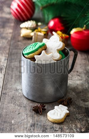 Christmas cookies in a metal cup and Christmas decoration on a rustic wooden table