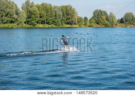 young man is wakeboarding on the lake