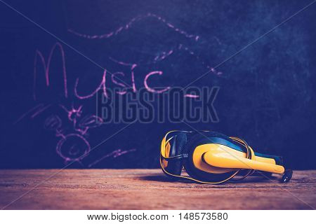 Yellow headphones on old wooden background .