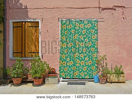 A door covered by a cloth and a window in an historic building in Marano Lagunare in Friuli Venezia Giulia north east Italy.