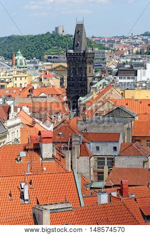 Aerial view of the traditional red roofs of the city of Prague Czech Republic with the Powder tower in the distance. It is one of the original city gates from 11th century.
