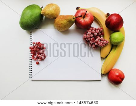 Colorful organic fresh fruit mix and open notepad paper page isolated on white background. Diet fitness healthy sport eating food nutrition lifestyle concept with empty copy space close up view