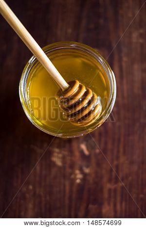 Fresh natural honey in a jar with honey spoon on a wooden rustic vintage table, selective focus