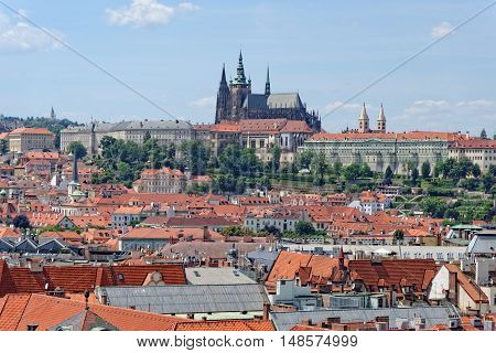 Aerial view of the traditional red roofs of the city of Prague Czech Republic with the Prague Castle - Hradcany in the background.