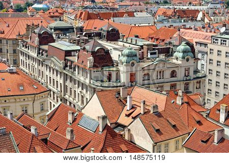 Aerial view of the traditional red roofs of the city of Prague Czech Republic. The Prague New City Hall is seen with its sculptures on the roof.