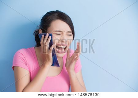woman have toothache isolatedon blue background asian