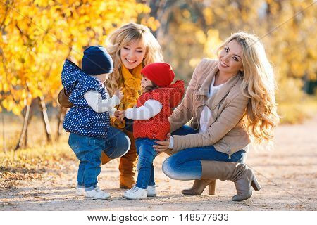 Two beautiful young mothers,blonde with long curly hair,dressed in blue jeans and leather jackets,walk in the Park day on the background of beautiful yellow autumn nature with young daughters,dressed in a red and blue jacket and blue jeans