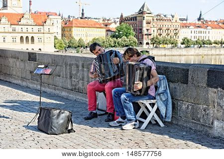 PRAGUE CZECH REPUBLIC - JULY 3 2014: Performance of street musicians on the Charles Bridge. Busking is legal form of earning money on Prague Streets.