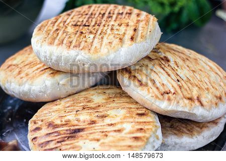 Georgian traditional dish khachapuri, pastry flat cake cheese-filled bread fried on the grill, BBQ. Fresh hot tasty street food in the market. Cooking food. Preparation dish of Middle Eastern cuisine.