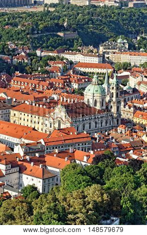 Aerial view of St. Nicholas church in the Lesser town district and the red roofs of Prague Czech Republic.