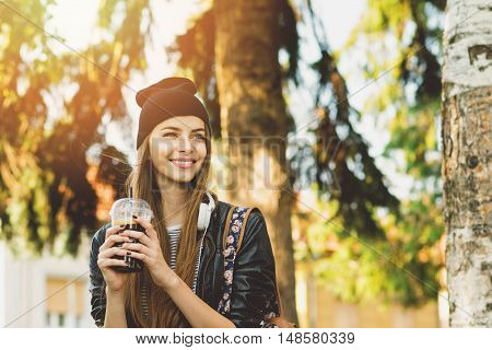Millennial teenage girl with coffee and headphones in park in autumn. Cool urban modern young woman smiling, drinking takeaway drink. Medium retouch, natural light.