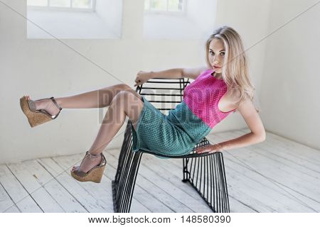 Beautiful and young model posing on a chair