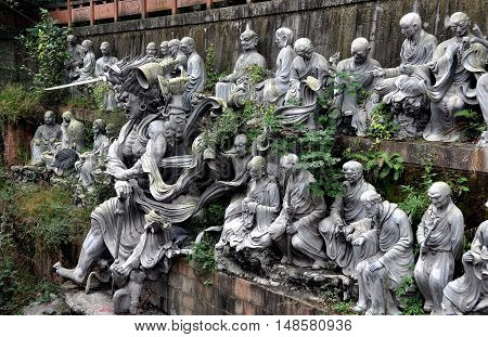Mianyang China - October 15 2010: Carved tableaux of life size Buddha statues at the Sheng Shui Buddhist temple which dates to the Tang and Qing Dynasties