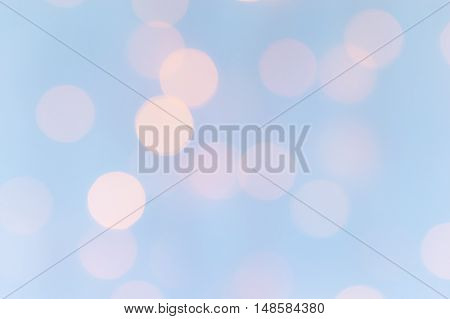 Sparkly bokeh lights background pastel pale blue and pink.