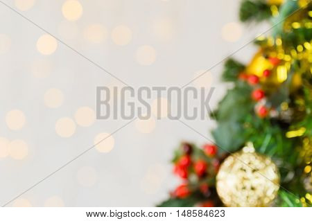 Out of focus festive Christmas close up of tree decorated with gold baubles tinsel and holly berries. Bokeh background copy space.