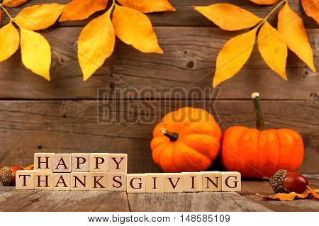 Happy Thanksgiving Wooden Blocks Against A Rustic Wood Background With Autumn Leaves And Pumpkins
