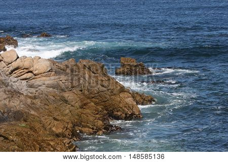 This is an image of the incoming tide and rocks taken on a sunny day at Asilomar Beach, in Pacific Grove, California.