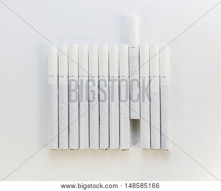 Cigarette with a white filter laid out in a row on a white background