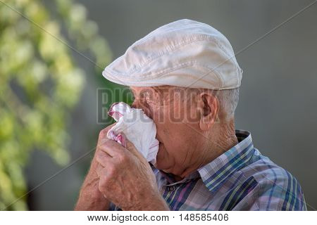 Old Man Blowing Nose In Napkin