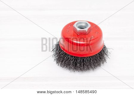 One red metal brush on wooden table