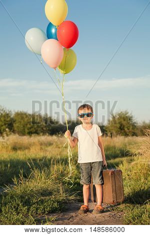 Happy little boy playing on road at the day time. He standing in the field and holding in hands suitcase and balloons. Kid having fun on the nature. Concept of happiness.