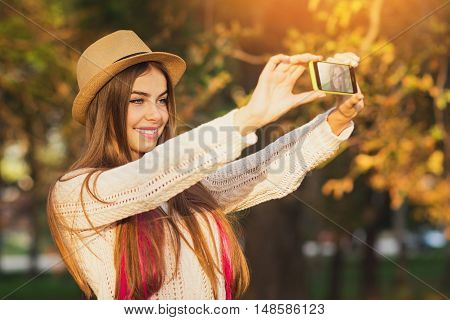 Beautiful teenage girl taking a selfie in park in autumn. Portrait of cute young woman with long blonde and pink hair, in fedora hat and crochet white sweater in fall. Vibrant colors, retouched.