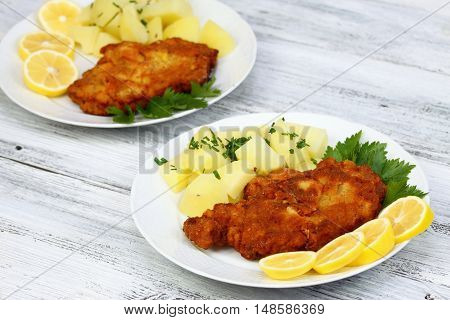Wiener schnitzel and boiled potatoes with chopped chives sliced lemon and lettuce