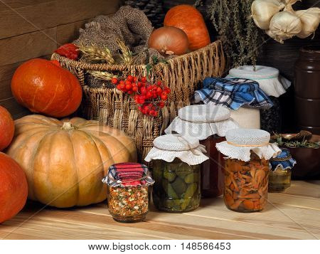 Domestic supplies of pickled cucumbers and mushrooms in the glass jars on wooden shelf. Pantry. Pumpkin dishes drawer for vegetables