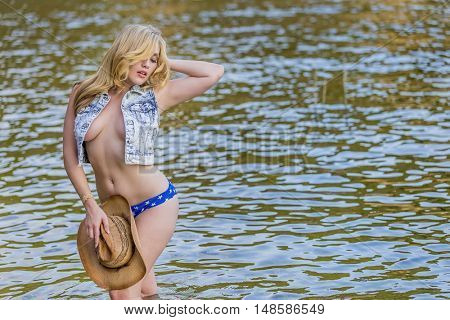 Blonde model posing near water in an outdoor environment