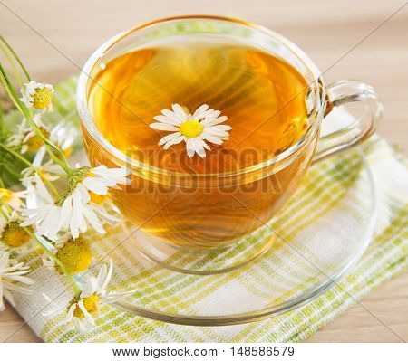 Chamomile tea in a transparent cup and a bouquet of daisies
