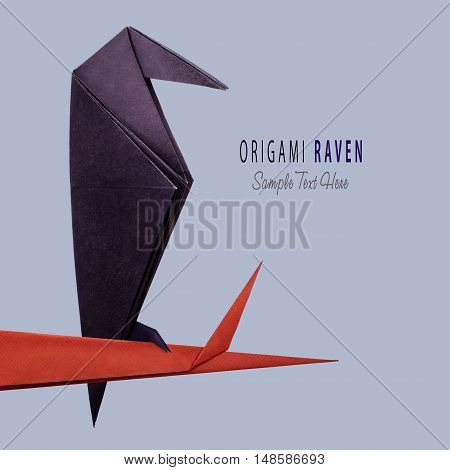 Origami paper halloween raven isolated on tree branch