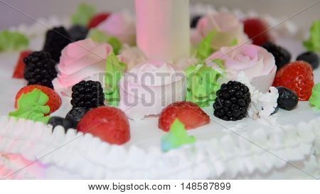 Festive white cake with cream and fruit. Whipped cream in the shape of a rose sprinkled with strawberries and raspberries. Sweet food for the anniversary.