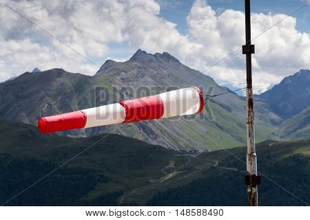 Red And White Striped Windsock Dramatic Clouds Mountains In Background