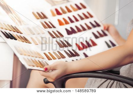 Young woman holding hair color swatches. Picking hair color.