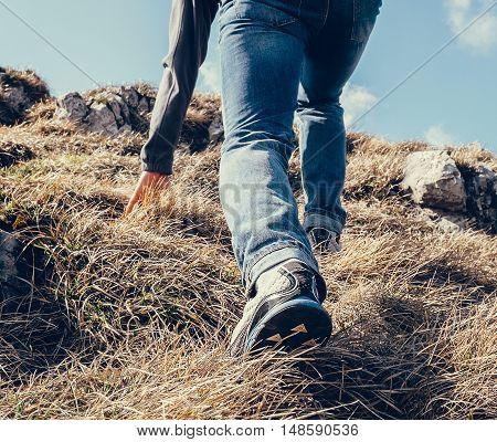 Close up imade climber legs make a last steps before peak
