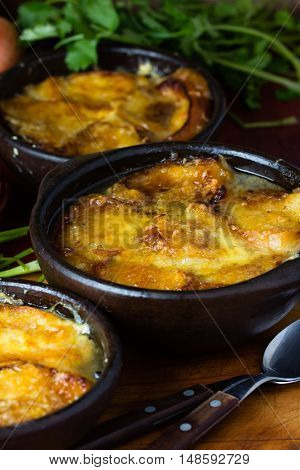 Onion soup with dried bread and cheddar cheese in rustic clay bolwls